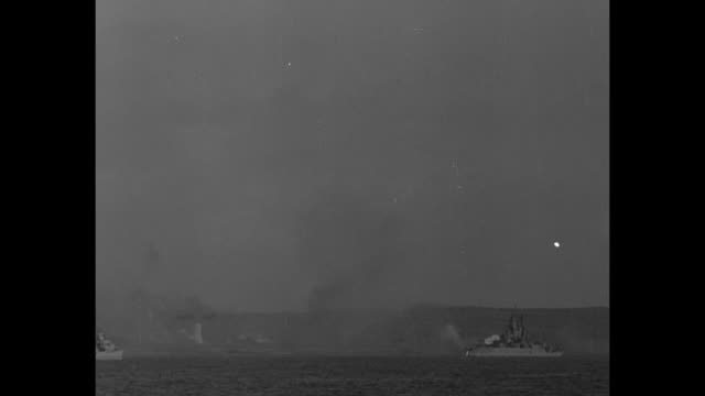 world war ii / pacific theater / iwo jima / ws mt suribachi and marines leaving beach / battleships and destroyers at sea firing / heavy smoke /... - battle of iwo jima stock videos and b-roll footage