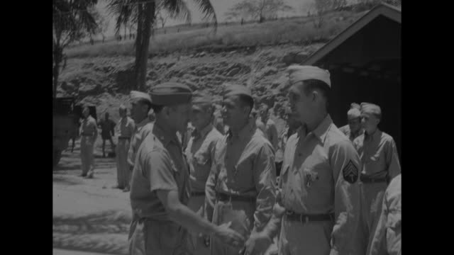 World War II / Pacific theater / medal ceremony with US Army Brig Gen Kenneth Walker / Walker shakes hand with soldiers and officer / CU officers and...