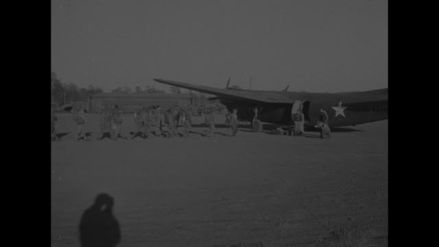 World War II / Pacific theater / several planes in air / US troops queue to board plane / plane being unloaded / WS B24 / troops boarding plane /...