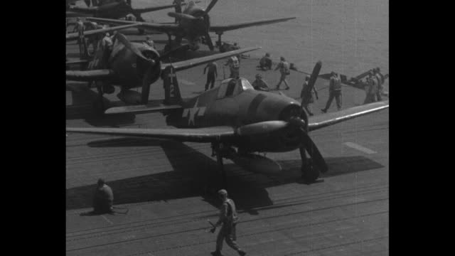 world war ii / pacific theater / the philippines / flight deck of aircraft carrier with planes being towed into position for takeoff / pilots walking... - guerra del pacifico video stock e b–roll