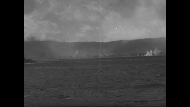 World War II / Pacific theater / US Marines descending from ship into landing craft / several fully loaded LCI crossing water to Saipan / shelling of...