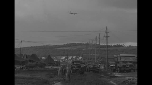 World War II / the Pacific / B29 coming in for a landing in the background of American military camp / crew fueling B29 / B29s sitting on tarmac /...