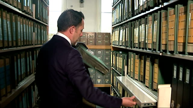 World War One Centenary Armistice Day commemorations London Imperial War Museum INT Reporter and Andrew Wakefield taking album from archive shelf
