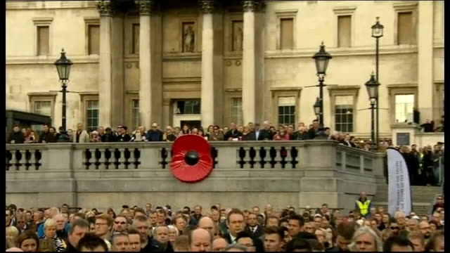 World War One Centenary Armistice Day commemorations Trafalgar Square Crowd standing outside for 2 minute silence with giant poppy on railings Crowd...