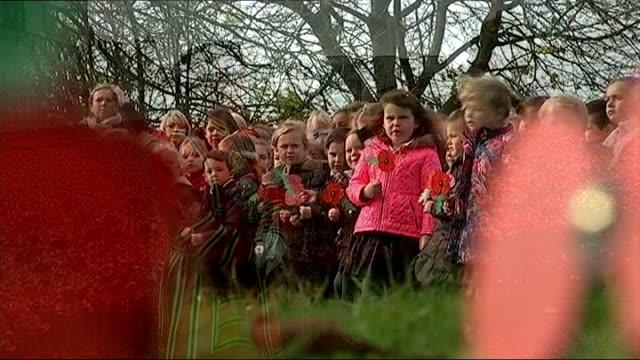 World War One Centenary Armistice Day commemorations Yeoman Warder Jim Duncan reading poem school children holdng poppies ceramic poppies SOT