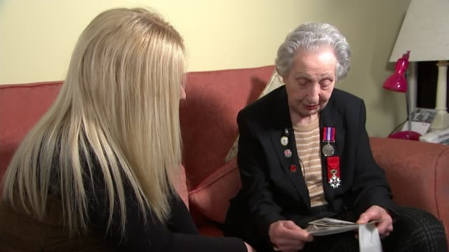 DDay landings switchboard operator to receive Legion d'honneur ENGLAND INT Marie Scott looking at photographs and chatting with reporter SOT