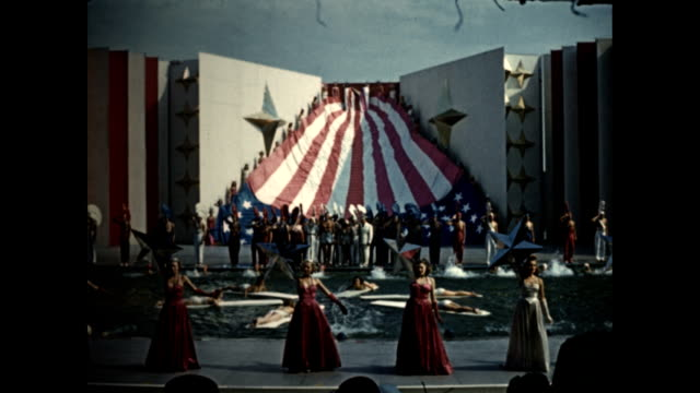world's fair aquacade finale people carrying state flags / women in red white and blue gowns walking down stairs around pool unfurling giant american... - new york stato video stock e b–roll
