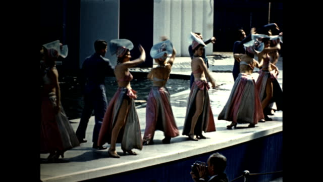 world's fair aquacade parade by pool of women in different elaborate costumes ws dancing revue couples dancing off on pool promenade / man and woman... - exhibition stock videos & royalty-free footage