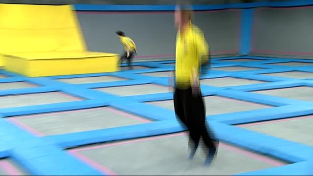 world's longest trampoline project; int man bouncing on giant trampoline at air hop trampoline park gvs men bouncing together on world's longest... - lunghezza video stock e b–roll