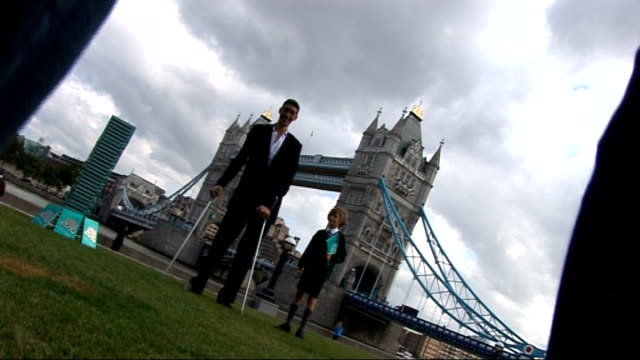 world's tallest man visits london: photocalls and interview; england: london: ext world's tallest man, 8 feet 1 inch tall sultan kosen, posing for... - inch stock videos & royalty-free footage