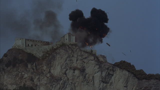 worm's-eye of a medieval castle exploding atop a sheer cliff. - gunpowder explosive material stock videos & royalty-free footage