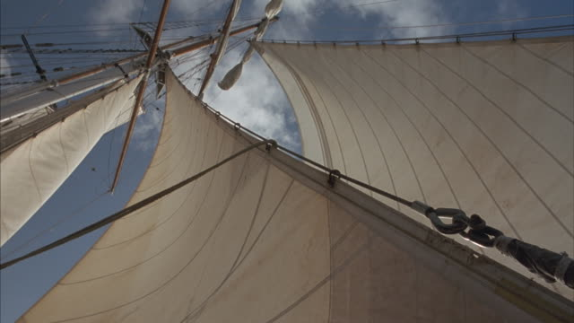 worm's-eye shot of the sails and mast of a sailing ship. - schiffsmast stock-videos und b-roll-filmmaterial
