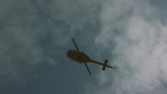 Worms-eye view of a model helicopter suspended by cables exploding.