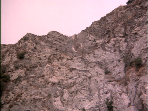 Worm's-eye view of a rocky cliff as a sports car careens over the edge and explodes.