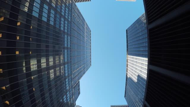vídeos de stock, filmes e b-roll de worm's-eye view of skyscraper buildings in metropolis. modern and urban city environment. - vista de baixo para cima