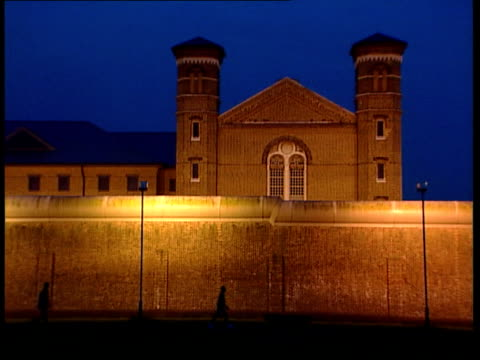wormwood scrubs report; dusk gv prison wall and part of building as distant figures in silhouette walking along alongside prison walls bars over cell... - no parking sign stock videos & royalty-free footage