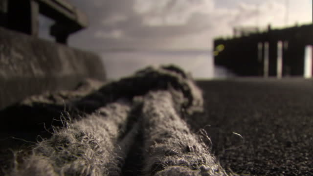 a worn and knotted rope lies near the ocean and a pier. - rope stock videos & royalty-free footage