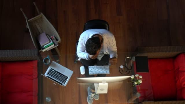 心配と疲れた中間成人男性医師は、彼のコンピュータ上の医学的な結果を読みます - 憂鬱点の映像素材/bロール