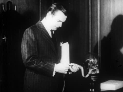 b/w 1929 worried businessman looking at ticker tape machine / newsreel - one mature man only stock videos & royalty-free footage