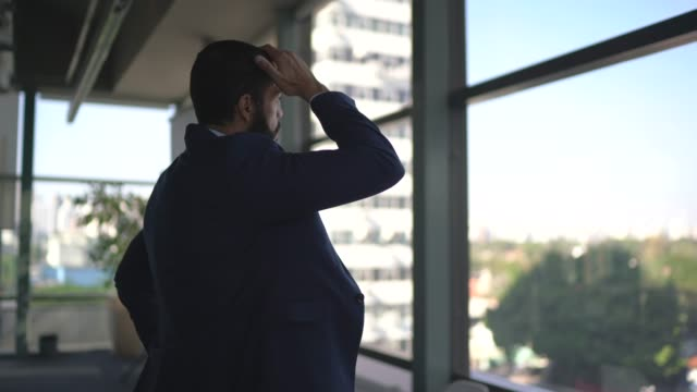 worried businessman looking through window contemplating on the office - worried stock videos & royalty-free footage