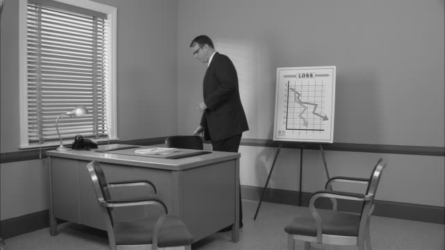 stockvideo's en b-roll-footage met b/w ms worried businessman pacing in office and checking watch in front of office with poster of graph indicating loss/ new york city - graph