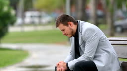 Worried businessman sitting on a bench