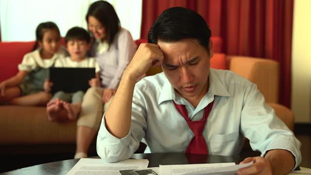 vídeos y material grabado en eventos de stock de un padre preocupado mirando la factura financiera en su mano, en el fondo de su familia jugando a la tableta. - finanzas familiares