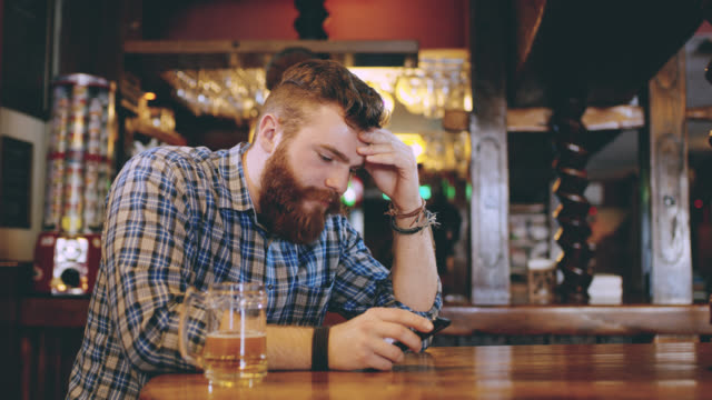 DS MS Worried hipster using a smartphone in the pub