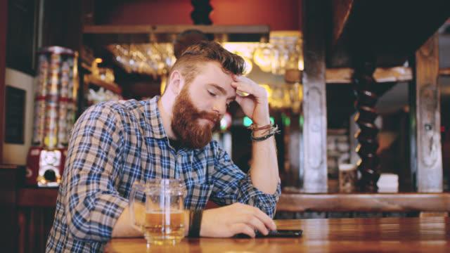 vídeos de stock, filmes e b-roll de ds ms preocupado olhando hipster usando um smartphone no pub - profissão na área de serviços