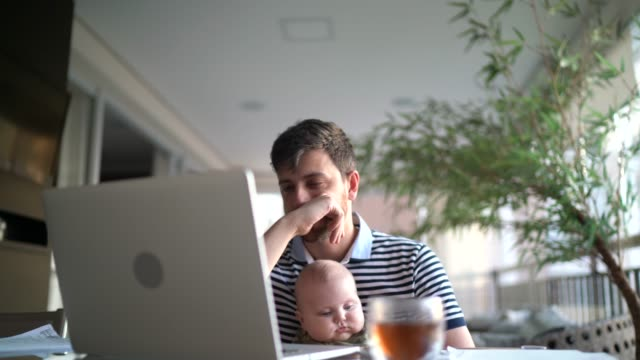worried man holding son and working with laptop at home - pandemic illness stock videos & royalty-free footage