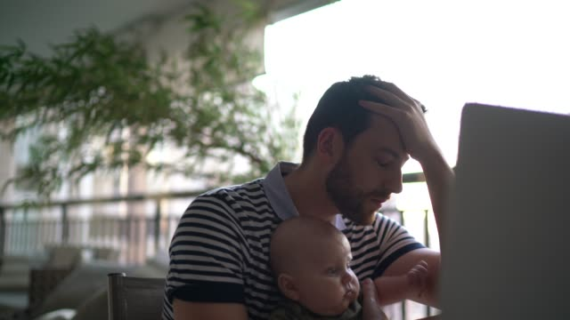 worried man holding son and working with laptop at home - tired stock videos & royalty-free footage