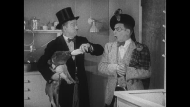 1934 worried man makes panicked man let go of explosive piglet, which follows them out the room - 1934 stock videos & royalty-free footage