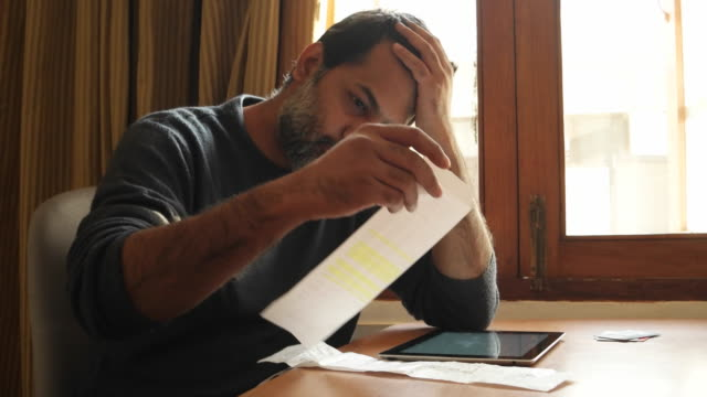 A worried man sorting his bills, seen with credit cards and a tablet