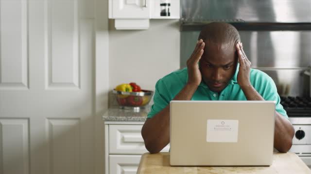 ms worried man using laptop in kitchen / edmonds, washington, usa - ノートパソコン作業点の映像素材/bロール