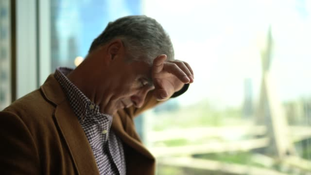 worried mature businessman close to window at office - hopelessness stock videos & royalty-free footage