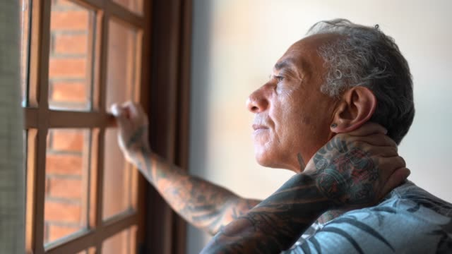 worried mature man looking through window contemplating and thinking at home - avoidance stock videos & royalty-free footage