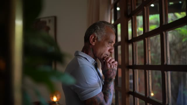 worried mature man looking through window contemplating and thinking at home - 50 54 years stock videos & royalty-free footage