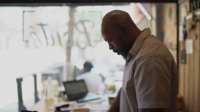 besorgter reifer mann besitzer arbeitet in seinem kleinen unternehmen - geschäftsinhaber stock-videos und b-roll-filmmaterial