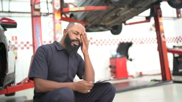 vídeos de stock, filmes e b-roll de mecânico preocupado trabalhando em reparo de automóveis - displeased
