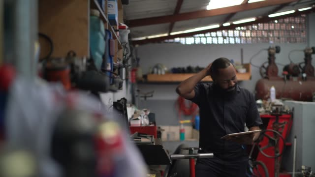 worried mechanic working with tablet in auto repair - mistake stock videos & royalty-free footage