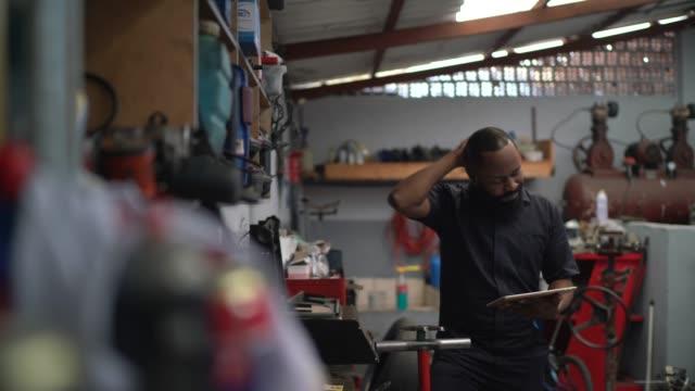 vídeos y material grabado en eventos de stock de mecánico preocupado que trabaja con la tableta en la reparación automática - mecánico de coches