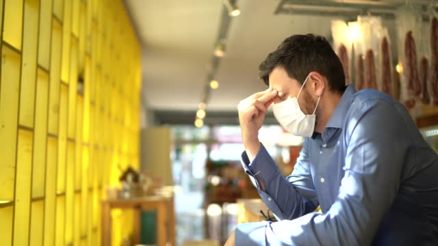 vídeos de stock e filmes b-roll de worried owner with face mask at his small business - sadness