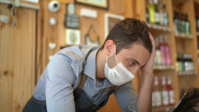 worried owner with face mask at his small business - emotional stress stock videos & royalty-free footage