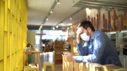 Worried owner with face mask using mobile phone at his small business