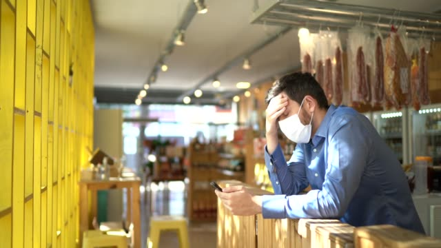 worried owner with face mask using mobile phone at his small business - bancarotta video stock e b–roll