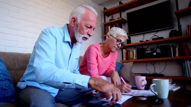vídeos de stock, filmes e b-roll de preocupado casal sênior contando as contas em casa - falência