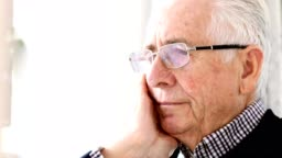 Worried Senior Man Sitting In Chair At Home