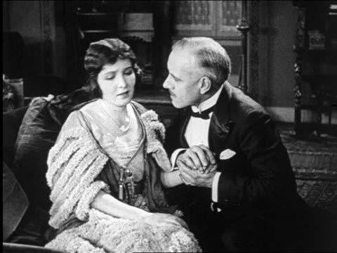 B/W 1922 worried woman turning away from lover in tuxedo / documentary