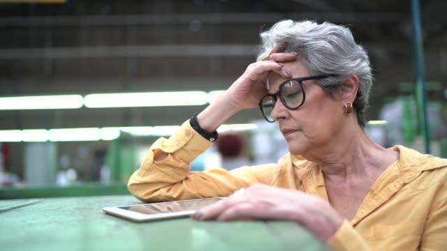 vidéos et rushes de femme inquiété travaillant dans l'usine - pression physique
