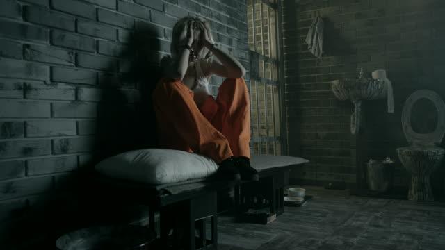angst frauen sitzen auf bett in gefängniszelle - gefängnis stock-videos und b-roll-filmmaterial